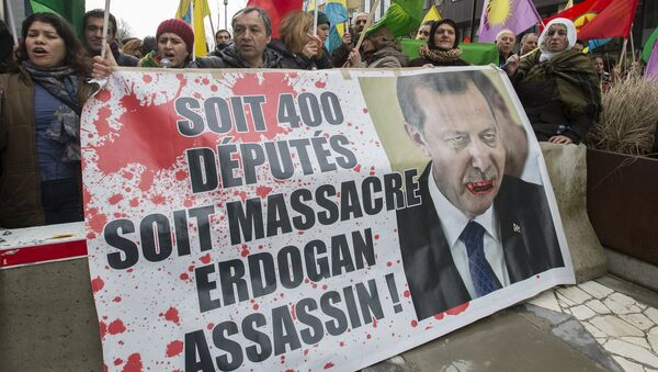 Kurdish people display a picture of Turkish President Tayyip Erdogan during a protest outside an EU-Turkey summit as the bloc is looking to Ankara to help it curb the influx of refugees and migrants flowing into Europe, in Brussels March 7, 2016 - Sputnik France