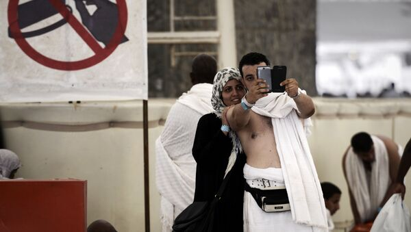 Muslim pilgrims pose for a selfie during the Jamarat ritual, the stoning of Satan, in Mina near the holy city of Mecca, on October 4, 2014. - Sputnik France