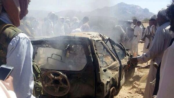 Yemenis gather around a burnt car after it was targeted by a drone strike killing three suspected al-Qaeda militants on January 26, 2015 between the Marib and Chabwa provinces, a desert area east of Sanaa. - Sputnik France