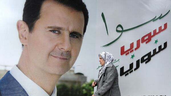 A Syrian woman walks past a placard bearing a portrait of President Bashar al-Assad in the city of Damascus on March 4, 2015. AFP PHOTO / LOUAI BESHARA - Sputnik France