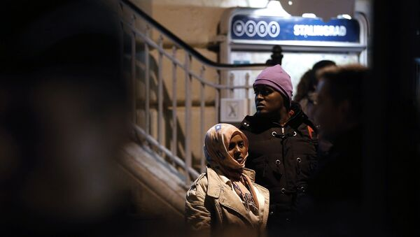 A woman and a man stand as they are evacuated by police officers and gendarmes from a makeshift camp under the Stalingrad railway station in Paris on March 30, 2016 - Sputnik France