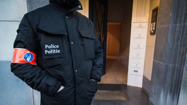 A police officer stands guard at the entrance of a building in Avenue des Cerisiers - Kerselarenlaan in Schaerbeek - Schaarbeek district in Brussels on March 25, 2016 where the Belgian police had a part of an anti-terrorist operation linked to Brussels attacks of March 22. - Sputnik France