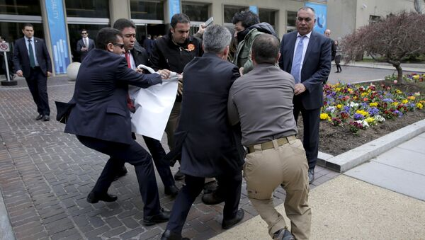 urkish security personnel struggle to take a sign away from protesters in front of the Brookings Institute before the arrival of Turkish President Recep Tayyip Erdogan in Washington. - Sputnik France