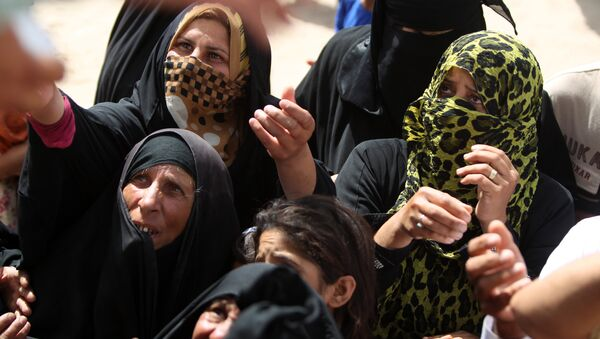 Displaced Iraqi women, who fled Ramadi, the capital of Anbar province, after it was seized by the Islamic State (IS) group, wait to get aid boxes at a makeshift camp for internally displaced persons (IDP) in Ameriyat al-Fallujah, 30 km south of Fallujah on June 6, 2015 - Sputnik France