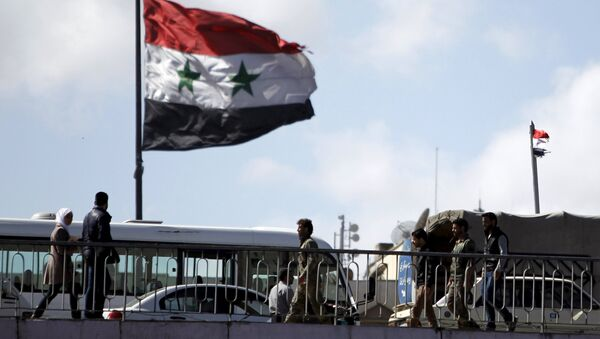 People walk near a Syrian national flag at the President bridge in Damascus, Syria March 14, 2016 - Sputnik France