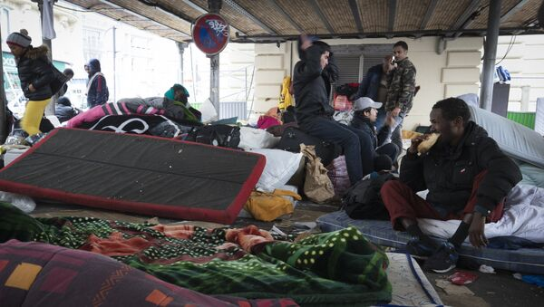 This photo taken on March 23, 2016 shows migrants in a makeshift camp of refugees and migrants from Afghanistan, Sudan, Somalia, Erytrea, set under the Paris elevated railroad near the Stalingrad subway station. - Sputnik France