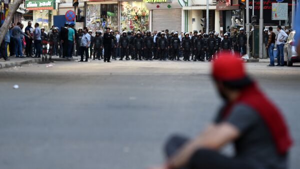 An Egyptian protester sits on the ground in front of riot policemen during a demonstration against a controversial deal to hand two islands in the Red Sea to Saudi Arabia on April 15, 2016 outside the Journalists' Syndicate in central Cairo. - Sputnik France