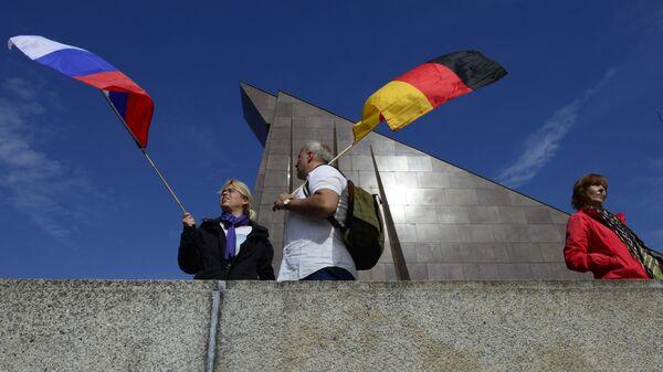 Des touristes avec des drapeaux russe et allemand - Sputnik France