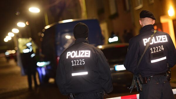 Armed police stand guard as others search a van at the scene in the Karl-Elsasser Street in Berlin's southern suburb of Britz on November 26, 2015. German police detained two suspects in a series of raids targeting Islamists in Berlin and said they were examining a suspicious object - Sputnik France