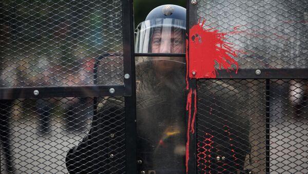 Полицейский стоит в оцеплении во время акции протеста профсоюзов в Париже - Sputnik France