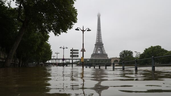 A picture taken on June 2, 2016 shows the river Seine bursting its banks next to the Eiffel Tower in Paris. Officials were putting up emergency flood barriers on June 2 along the swollen river Seine after days of torrential rain -- including near the Louvre, home to priceless works of art. - Sputnik France