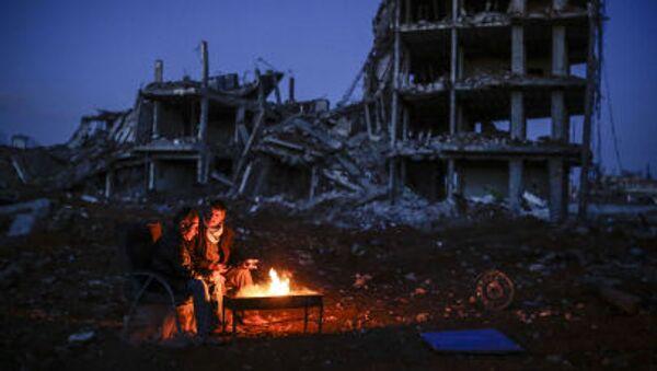 Курды сидят у костра среди разрушенного города Кобани - Sputnik France