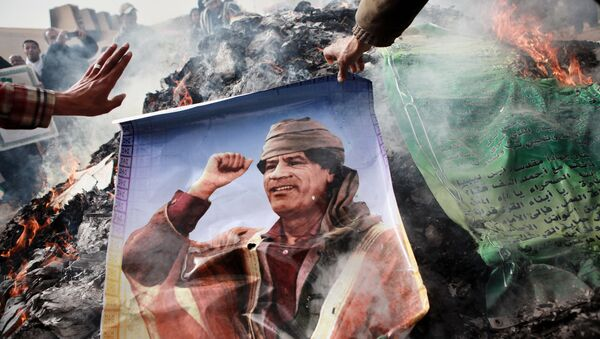 Un habitant de Benghazi (Libye) brûlant un portrait de Mouammar Kadhafi - Sputnik France
