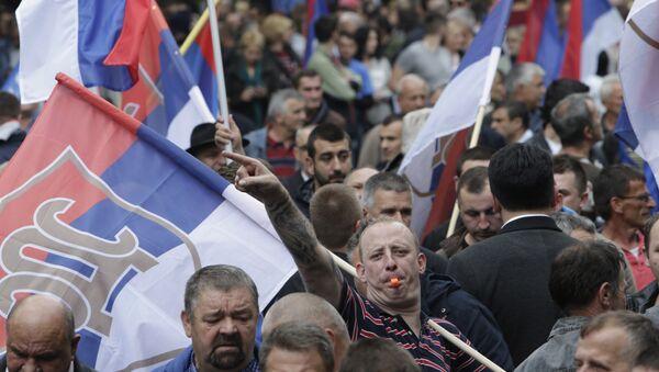 Un Serbe bosniaque porte le drapeaux lors d'une manifestation à Banja Luka, en Bosnie, le samedi 14 mai 2016 - Sputnik France
