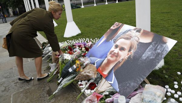 A woman leaves a floral tribute next to a photograph of murdered Labour Member of Parliament Jo Cox in Parliament Square, London, Britain June 17, 2016 - Sputnik France