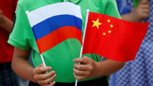 Un enfant tient des drapeaux russe et chinois lors de la cérémonie d'accueil du président russe Vladimir Poutine à Pékin - Sputnik France