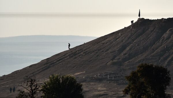 Alleged Islamic State (IS) militants stand next to a black IS flag atop a hill in at the eastern part of the Syrian town of Ain al-Arab, known as Kobane by the Kurds, as seen from the Turkish-Syrian border in the southeastern town of Suruc, Sanliurfa province, on October 7, 2014. - Sputnik France