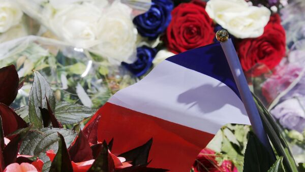A bouquet of flowers and a French flag is seen as people pay tribute near the scene where a truck ran into a crowd at high speed killing scores and injuring more who were celebrating the Bastille Day national holiday, in Nice, France, July 15, 2016. - Sputnik France