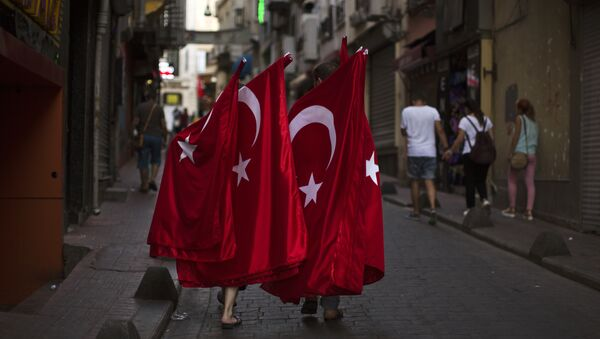 Two men carry Turkish flags for selling as they walk along a street in downtown Istanbul, Sunday, July 17, 2016. - Sputnik France