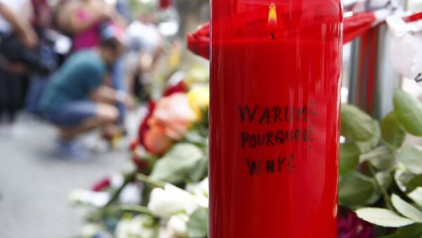 A candle with the words 'Why?' written upon it is placed next to flowers near the Olympia shopping mall, where yesterday's shooting rampage started, in Munich, Germany July 23, 2016. - Sputnik France