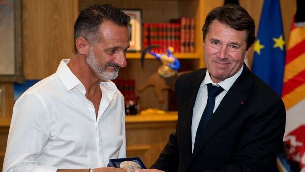 President of the Provence Alpes Cote d'Azur region and former Nice mayor Christian Estrosi (R) gives to Franck, one of the three 'heroes' of the July 14 attack in Nice, the city's medal at the City hall in Nice, southeastern France, on July 25, 2016. - Sputnik France