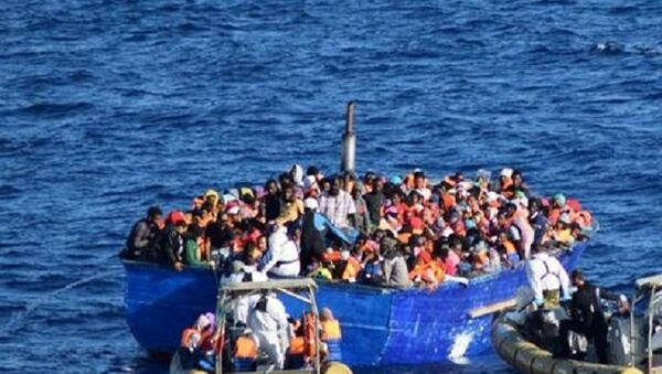 Migrants sit in their boat during a rescue operation by Italian navy ship Borsini (unseen) off the coast of Sicily, Italy, in this handout picture courtesy of the Italian Marina Militare released on July 19, 2016. - Sputnik France