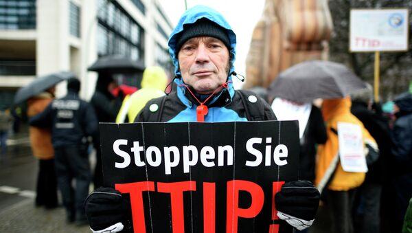 A protester holds up a sign, reading: Stop TTIP! (Transatlantic Trade and Investment Partnership) - Sputnik France