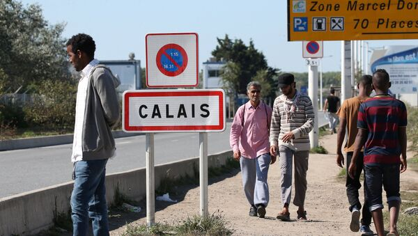 Migrants pass by a road sign as they leave the northern area of the camp called the Jungle in Calais, France, September 7, 2016. - Sputnik France