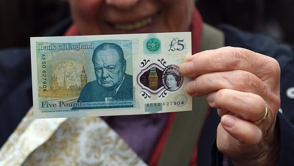 A woman holds up a new £5 (6.5 euros, $7.2) banknote bearing the image of wartime leader Winston Churchill at its unveiling by the Bank of England at Blenheim Palace in Woodstock on June 2, 2016. - Sputnik France