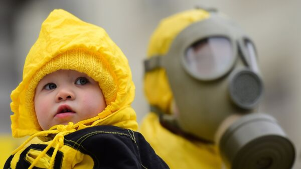 A child is pictured next to an anti-nuclear activist wearing a gas mask during a protest against the lack of safety of Belgian nuclear power plants, outside the Belgian Interior Ministry in Brussels, February 1, 2016, during a meeting of Germany's Environment Minister with Belgium's Interior Minister. - Sputnik France