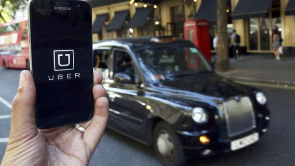 A photo illustration shows the Uber app logo displayed on a mobile telephone, as it is held up for a posed photograph in central London, Britain August 17, 2016. - Sputnik France