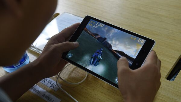 A customer plays a game on a Xiaomi Mi Pad tablet at a Xiaomi service center in Beijing on August 5, 2015. - Sputnik France