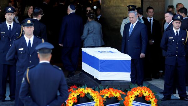 Israeli Prime Minister Benjamin Netanyahu (C) stands next to the flag-draped coffin of former Israeli President Shimon Peres, as he lies in state at the Knesset plaza, the Israeli parliament, in Jerusalem September 29, 2016. - Sputnik France