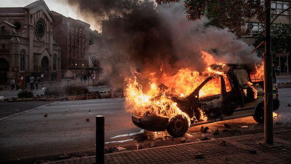 Горящий автомобиль в Йоханнесбурге, где прошли студенческие протесты - Sputnik France