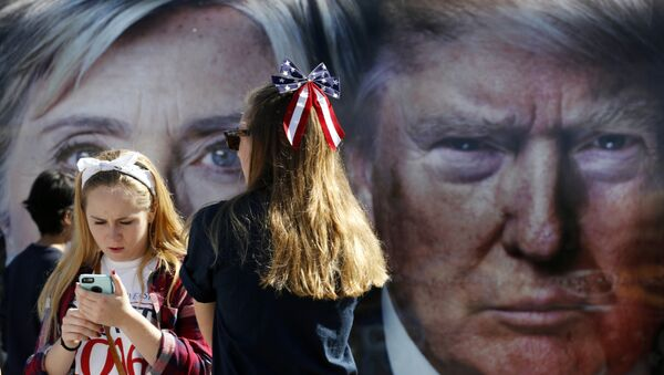 People pause near a bus adorned with large photos of candidates Hillary Clinton and Donald Trump before the presidential debate. - Sputnik France