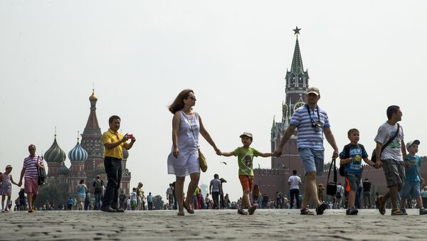 People walk through Red Square with the St. Basil's Cathedral, left, and the Spasskaya Tower, right, in the background, in Moscow, Russia, Sunday, July 24, 2016. - Sputnik France