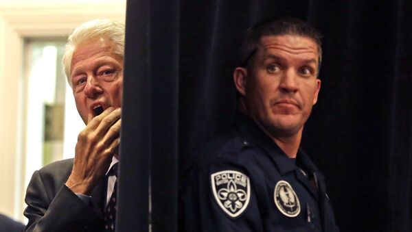 A Baton Rouge police officer stands post while former President Bill Clinton, left, watches from backstage before he is introduced to speak at a campaign event for Sen. Mary Landrieu, D-La., in Baton Rouge, La., Monday, Oct. 20, 2014. - Sputnik France