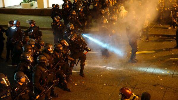 Un policier arrose la foule avec un irritant lors d'une manifestation contre l'élection du républicain Donald Trump comme président des États-Unis à Portland, Oregon, États-Unis le 12 Novembre 2016 - Sputnik France