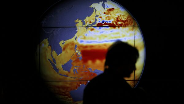 A woman walks past a map showing the elevation of the sea in the last 22 years during the World Climate Change Conference 2015 (COP21) at Le Bourget, near Paris, France, December 11, 2015 - Sputnik France