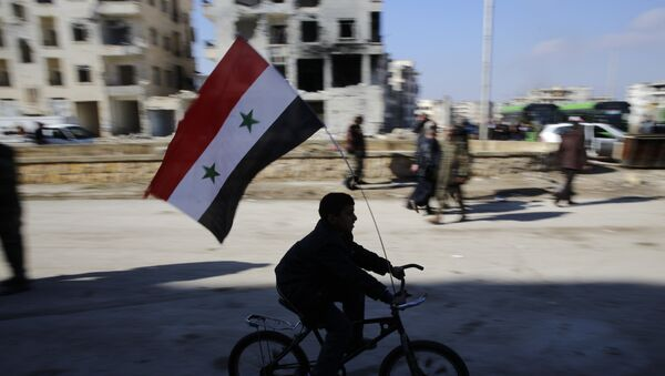 A Syrian boy rides a bike adorned with a Syrian flag as Syrians families, who were displaced from east Aleppo last month, return to their homes in the Hanano district of eastern Aleppo, Syria, Sunday, Dec. 4, 2016. - Sputnik France