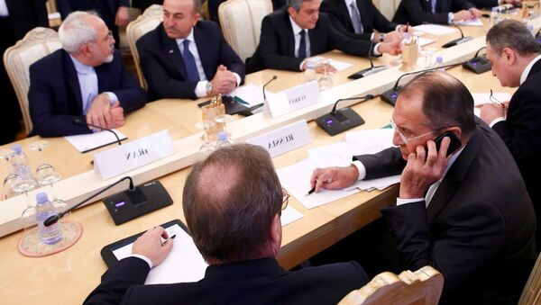 Foreign ministers, Sergei Lavrov (L, front) of Russia, Mevlut Cavusoglu (2nd R, back) of Turkey, Mohammad Javad Zarif (R, back) of Iran, and members of the delegations attend a meeting in Moscow, Russia, December 20, 2016. - Sputnik France