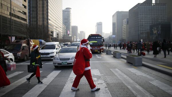 A man dressed as Santa Claus walks on zebra crossing during a Christmas charity event in central Seoul, South Korea, December 24, 2015 - Sputnik France