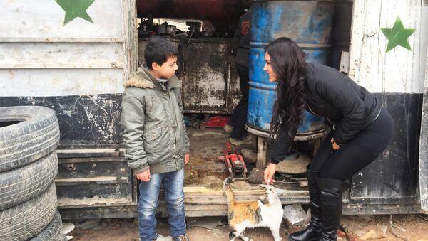 Carla Ortiz avec un enfant en Syrie - Sputnik France