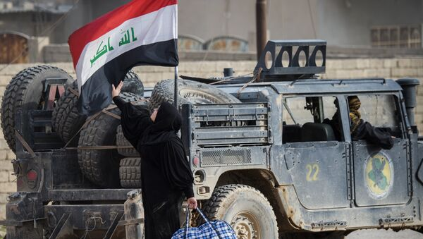An Iraqi woman fleeing the fighting touches her country's national flag mounted on a security forces vehicle as she reaches an area held by Iraqi Special Forces 2nd division in the Samah neighbourhood of Mosul on November 15, 2016. - Sputnik France