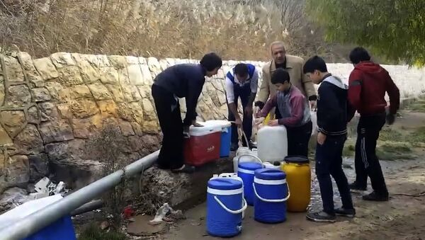 This frame grab from video provided By Yomyat Kzefeh Hawen Fi Dimashq (Diary of a Mortar Shell in Damascus), a Damascus-based media outlet that is consistent with independent AP reporting, shows Syrian residents filling up buckets and gallons of spring water from a pipe on the side of the road, in Damascus, Syria - Sputnik France