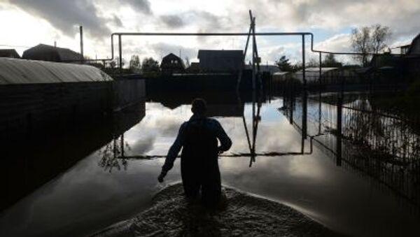 Мужчина идет мимо подтопленных дачных участков в районе поселка Мочище - Sputnik France