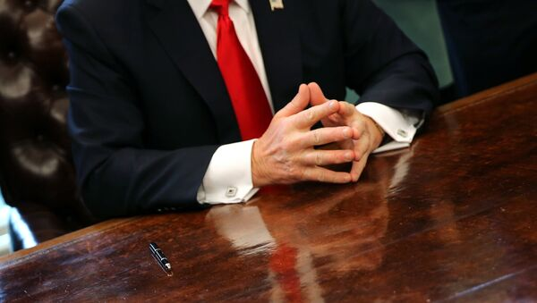 U.S. President Donald Trump sits at the Oval Office of the White House after signing an executive order cutting regulations in Washington U.S., January 30, 2017. - Sputnik France