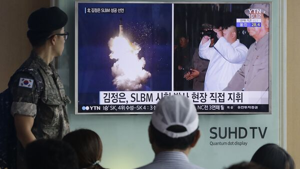 South Korean army soldier watches a TV news program showing images published in North Korea's Rodong Sinmun newspaper of North Korea's ballistic missile believed to have been launched from underwater and North Korean leader Kim Jong-un, at Seoul Railway station in Seoul, South Korea (File) - Sputnik France