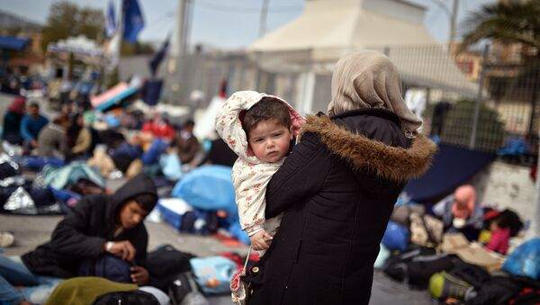 A Syrian woman holds her child at the port of Chios on April 3, 2016 as refugees and migrants who broke out from Chios detention camp, stand in the port of the city. - Sputnik France