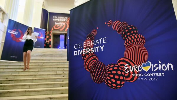 An employee walks past a placard bearing the official logo of the Eurovision Song Contest 2017 depicting a traditional Ukrainian necklace with the slogan reading Celebrate Diversity, on January 31, 2017 in Kiev. - Sputnik France